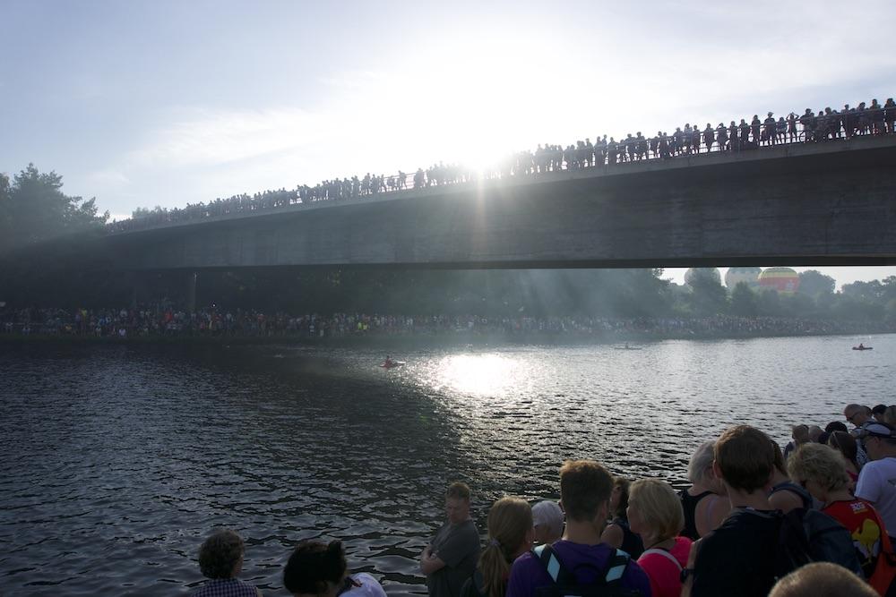 Zahlreiche Zuschauer begleiten die Athleten am Main-Donau-Kanla bei der ersten Disziplin, dem Schwimmen